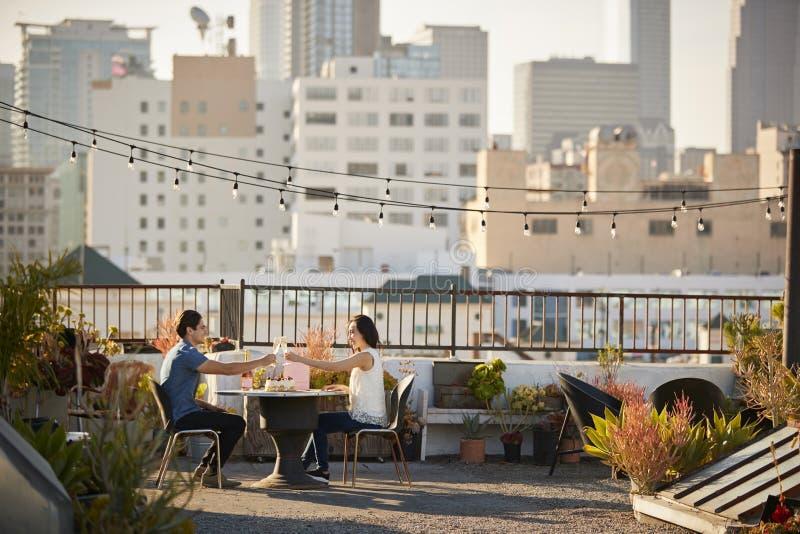 做多士的夫妇庆祝在屋顶大阳台的生日与城市地平线在背景中 免版税库存照片
