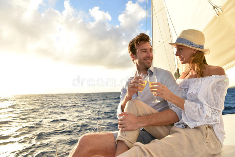 做多士的浪漫夫妇在巡航的小船在日落 免版税库存图片