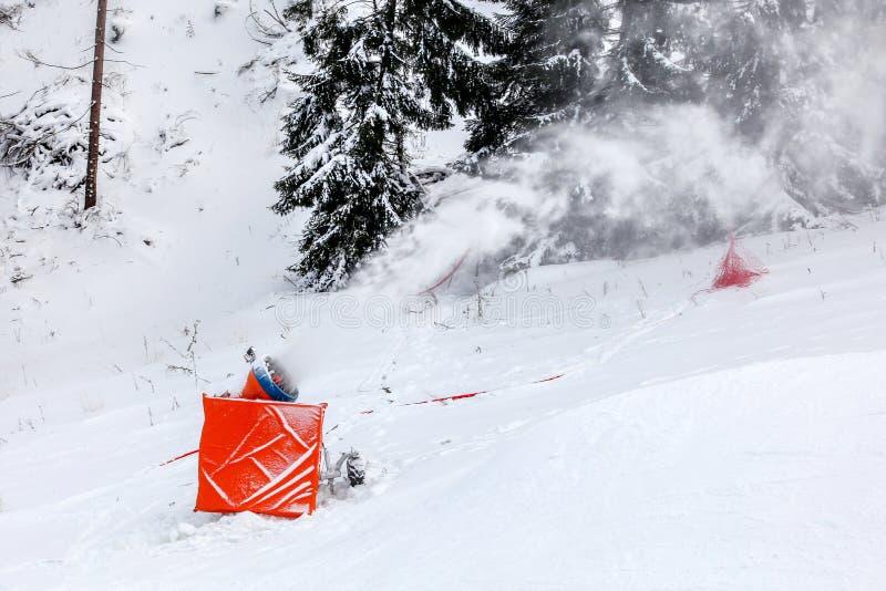 做大炮的雪喷洒在滑雪滑雪道的人为冰晶,树在背景中 图库摄影