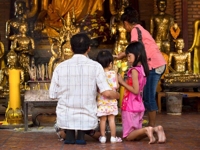 做奉献物在寺庙在阿尤特拉利夫雷斯, T的亚洲佛教家庭 免版税库存照片