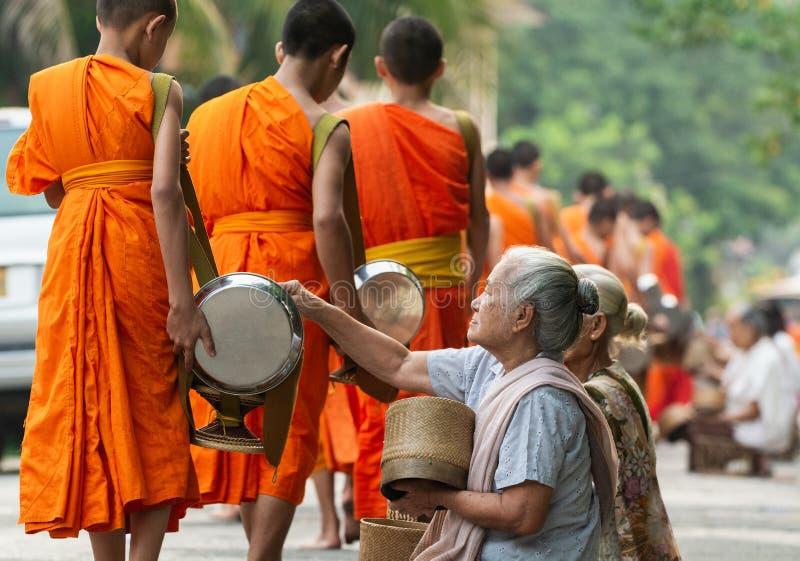做奉献物的老挝人民对和尚在传统救济仪式期间在琅勃拉邦市,老挝 库存照片