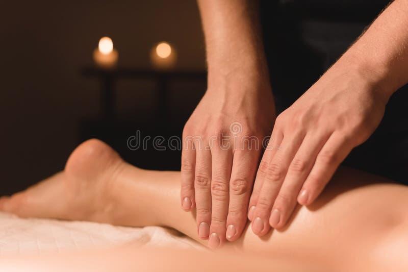 做女性腿的小牛按摩男性手特写镜头在有蜡烛的一个暗室在背景中 整容术和 免版税库存照片