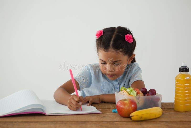 做她的家庭作业的女小学生反对白色背景 免版税图库摄影