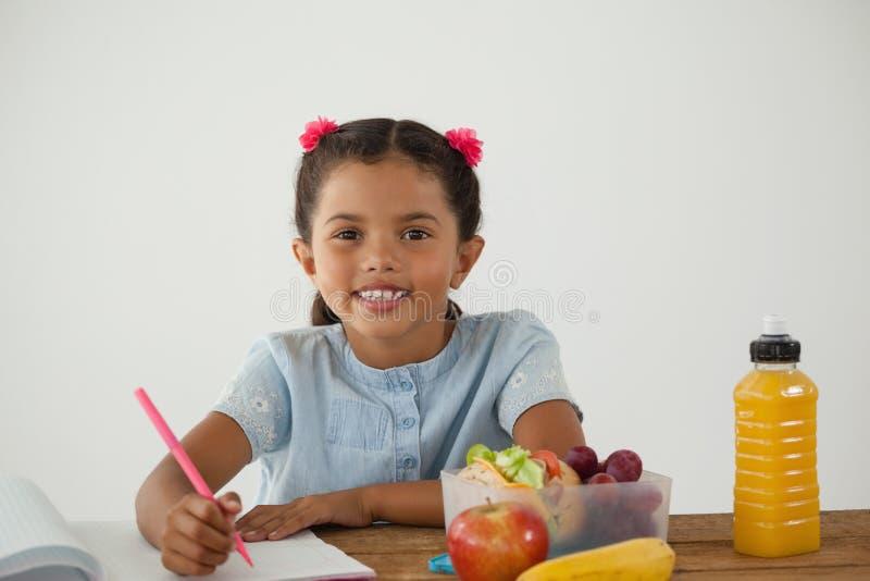 做她的家庭作业的女小学生反对白色背景 图库摄影
