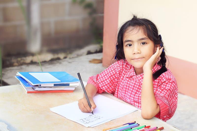 做她的家庭作业的小亚裔女孩在桌上 免版税库存照片