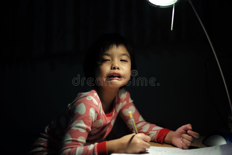 做她的家庭作业的小亚裔女孩画象在ligh下 库存图片