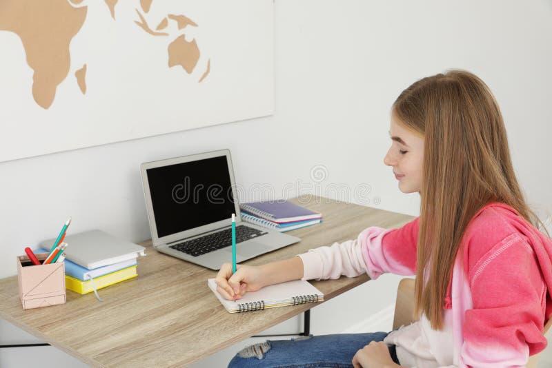 做她的家庭作业的少年女孩 库存图片