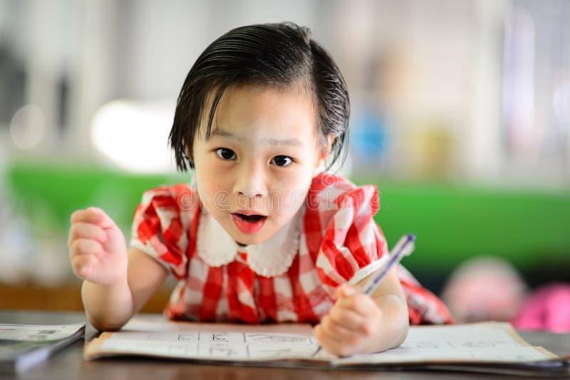做她的家庭作业的逗人喜爱的亚裔女孩 库存图片