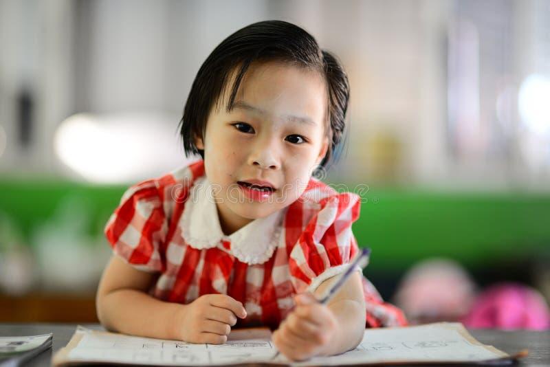 做她的家庭作业的逗人喜爱的亚裔女孩 免版税库存图片