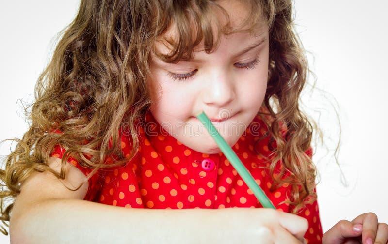 做她的家庭作业的逗人喜爱的小女孩 免版税库存照片