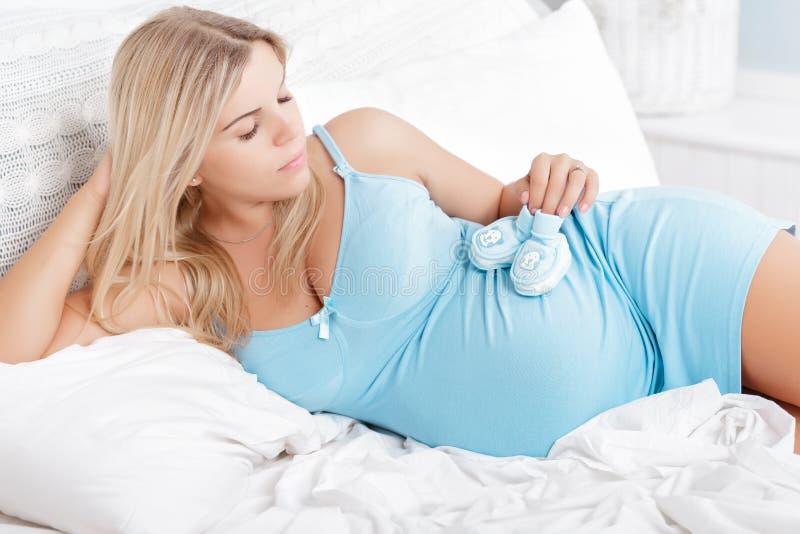 做她的构成的怀孕的白肤金发的妇女 库存图片