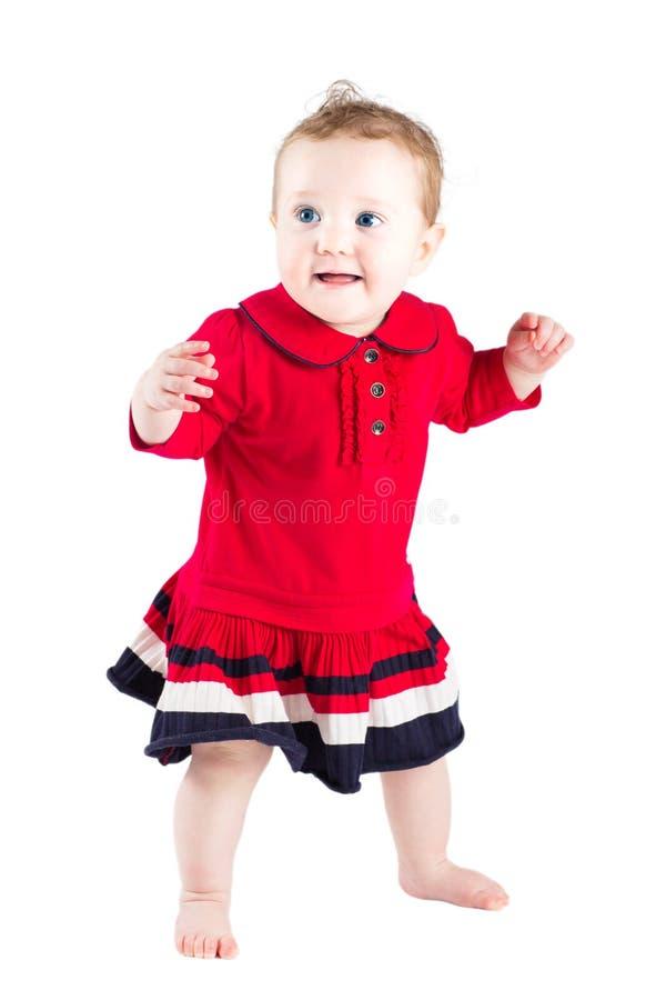 做她的第一步的一件红色礼服的美丽的女婴 库存照片