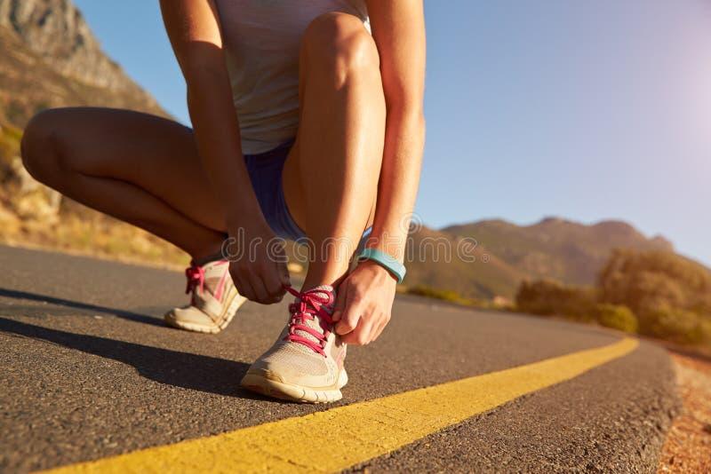 做她的鞋带的母慢跑者播种的射击 库存图片