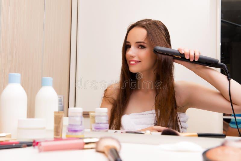 做她的头发的俏丽的妇女为党做准备 免版税库存图片