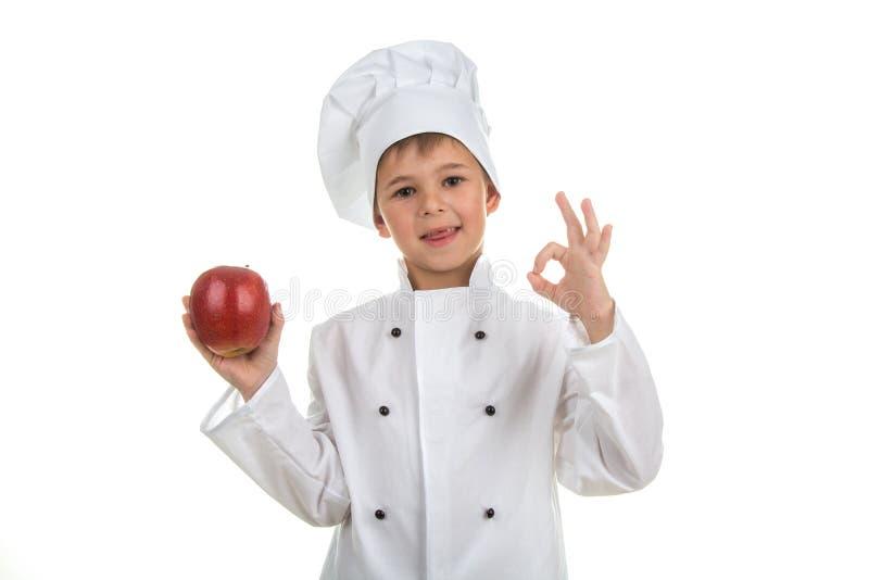 做好姿态和拿着红色苹果的逗人喜爱的小男孩佩带的厨师制服 免版税图库摄影