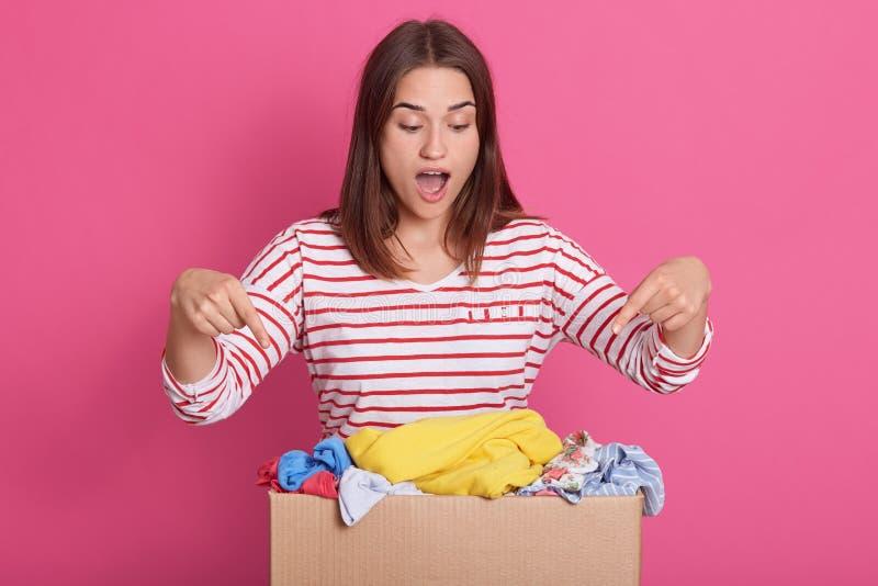 做姿态的热心正面志愿者的图片,指向包装有食指的箱子,广泛张她的嘴, 库存照片
