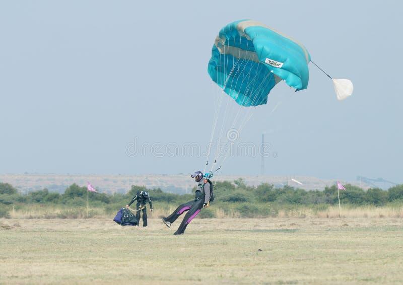 做安全着陆的黑非洲男性跳伞运动员在与操作的草 库存图片
