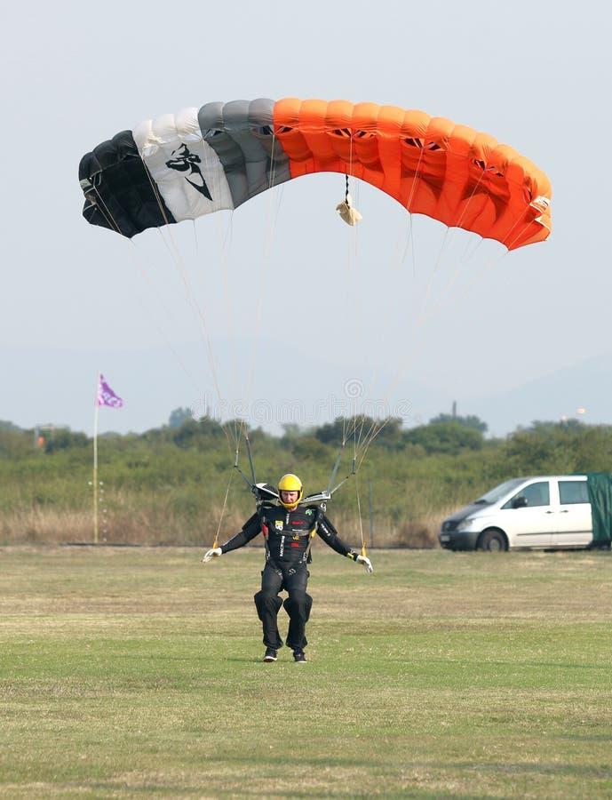 做安全着陆着陆的男性跳伞运动员在与开放bri的草 免版税库存照片