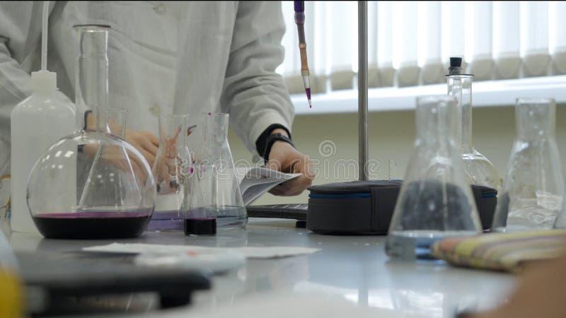 做实验的化验员在实验室 男性医疗或科学实验室研究员执行测试与蓝色液体 免版税库存图片