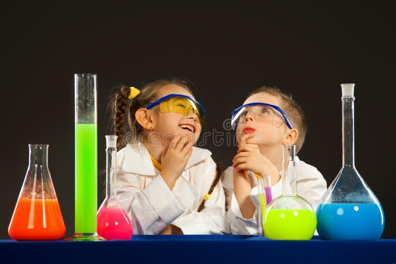 做实验的小男孩和女孩在实验室里 免版税库存图片