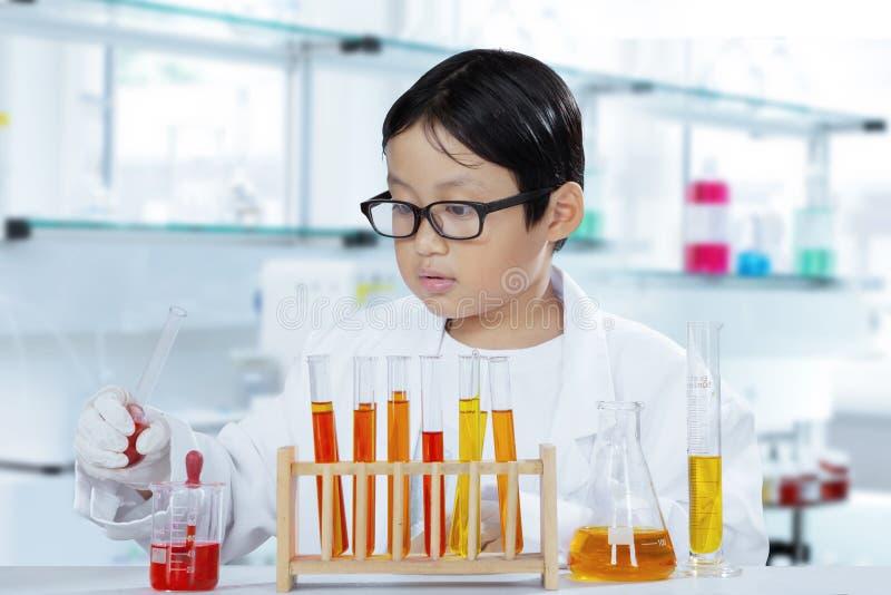 做实验的小男孩在实验室里 库存图片