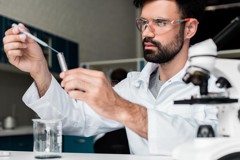 做实验的防护玻璃的男性科学家在化工实验室 免版税库存图片