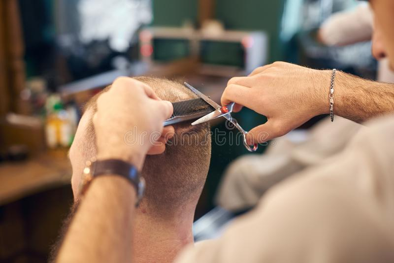 做客户的男性美发师短的理发在现代理发店 传统haircutting的概念与剪刀 免版税图库摄影