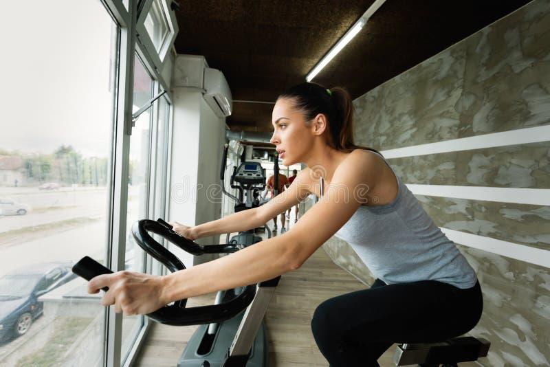 做室内骑自行车的锻炼的年轻美丽的妇女 免版税图库摄影