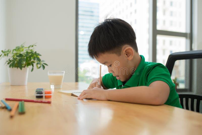 做家庭作业、上色页、文字和pai的逗人喜爱的微笑的男孩 库存图片