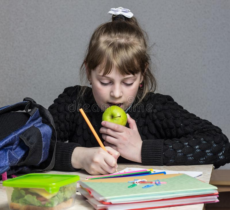 做家庭作业和吃苹果、绿色苹果和女小学生的女孩做家庭作业 免版税库存图片