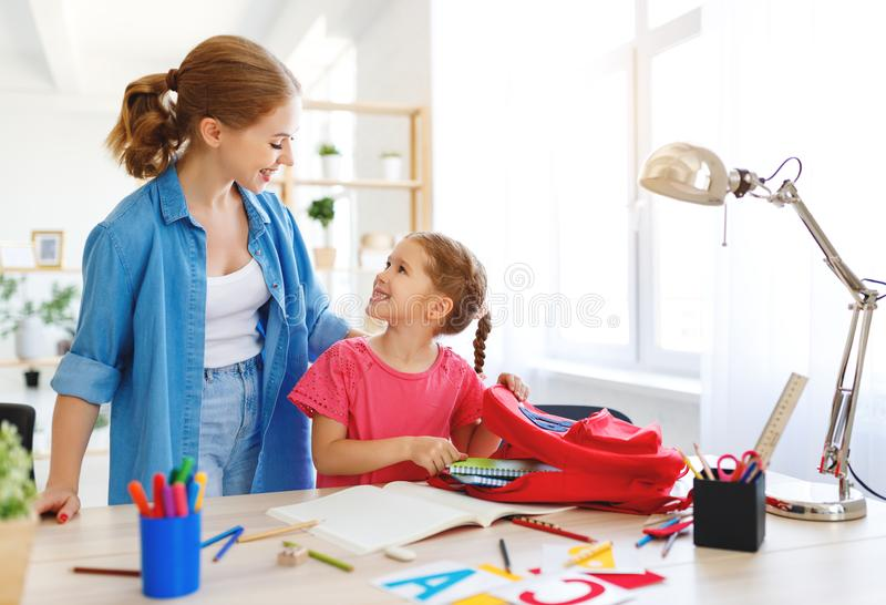 做家庭作业文字和读的母亲和儿童女儿 免版税库存照片