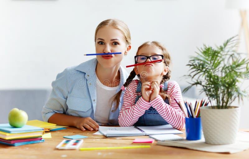 做家庭作业文字和读的滑稽的母亲和儿童女儿 免版税库存照片