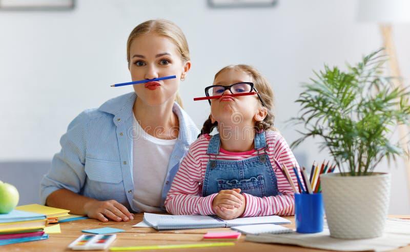 做家庭作业文字和readi的滑稽的母亲和儿童女儿 库存照片