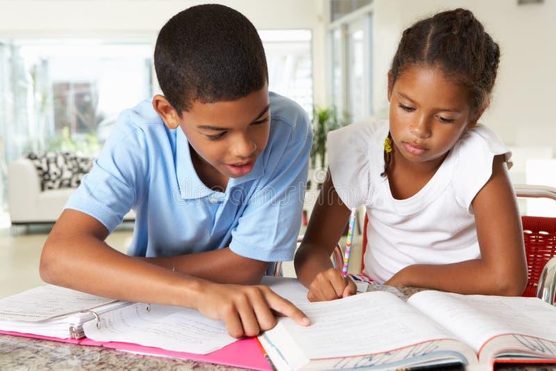 做家庭作业的两个孩子在厨房里 免版税图库摄影