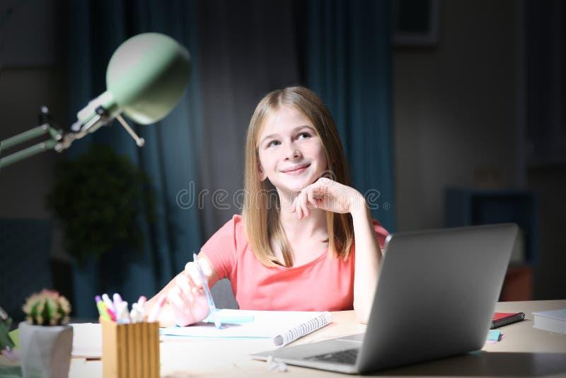 做家庭作业的十几岁的女孩在桌上 库存图片