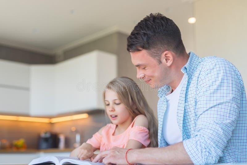 做家庭作业的微笑的家庭在厨房里 免版税库存照片