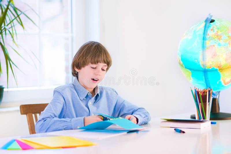 做家庭作业的微笑的小男孩 图库摄影