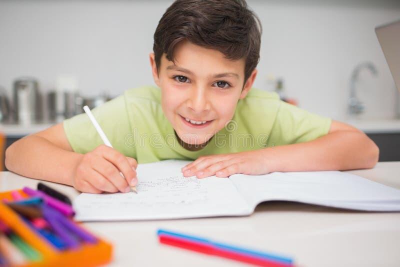 做家庭作业的微笑的男孩在厨房里 库存图片