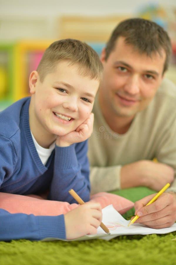 做家庭作业的父亲和儿子 免版税库存图片