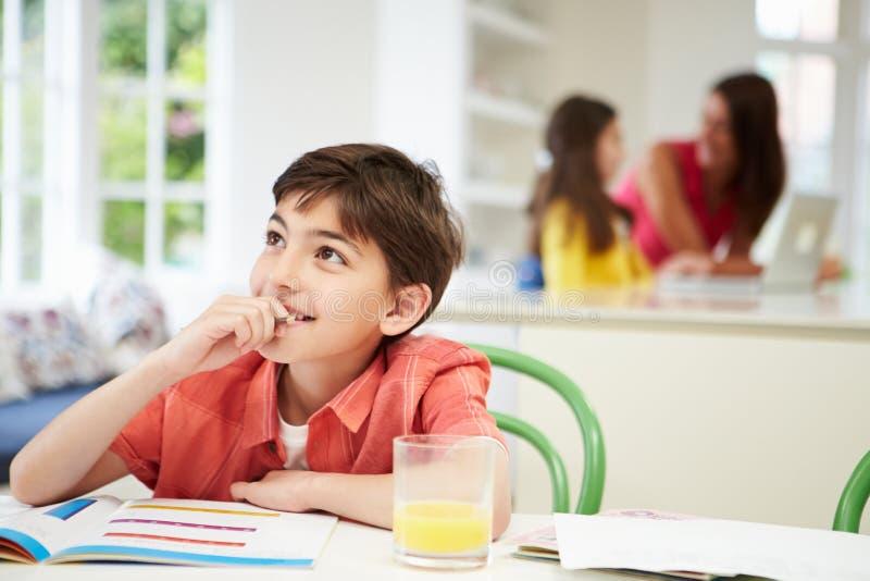 做家庭作业的男孩作为母亲和女儿 免版税库存照片