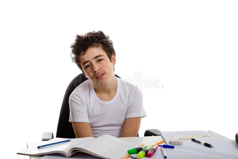 做家庭作业的疲乏的男孩 库存图片