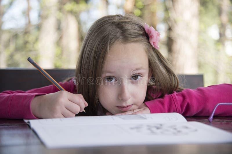 做家庭作业的美女在公园 免版税图库摄影