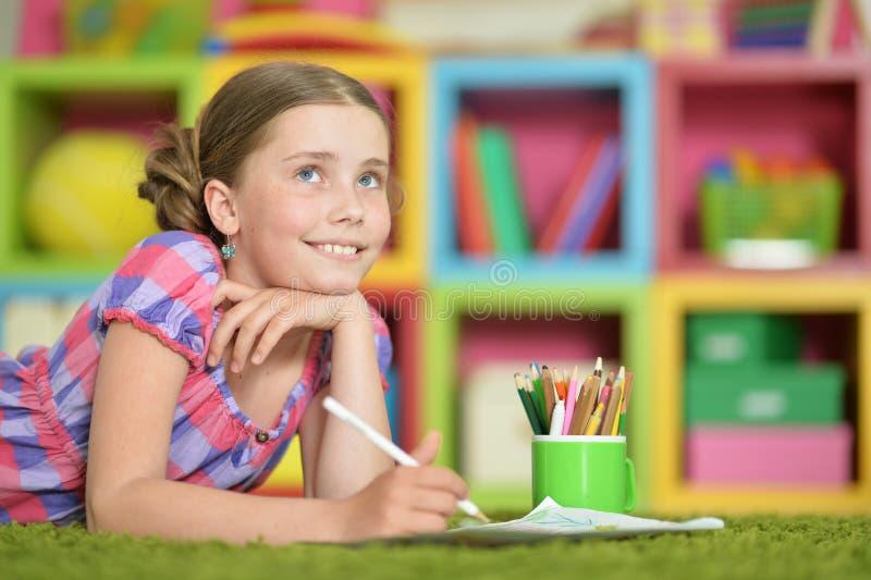做家庭作业的逗人喜爱的女小学生 库存图片