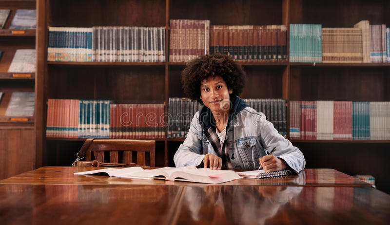 做家庭作业的年轻大学生在图书馆里 免版税库存图片