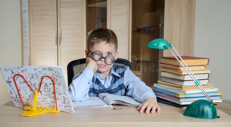 做家庭作业的滑稽的玻璃的疲乏的男孩 儿童困难了解 有的男孩他的家庭作业的问题 教育 库存照片