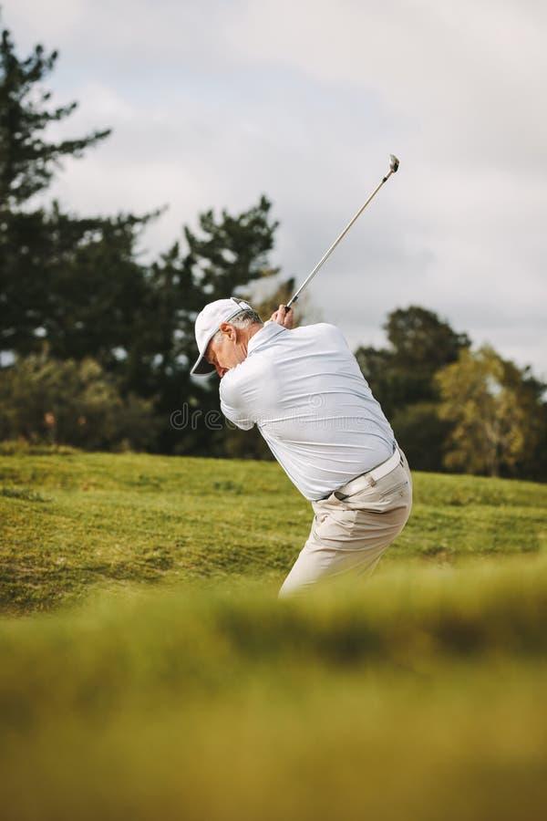 做射击的专业资深高尔夫球运动员由沙子地堡 库存照片