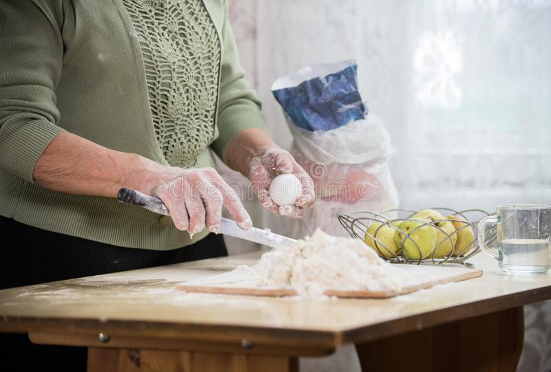 做小的饼的一个老妇人 拿着鸡蛋 库存照片