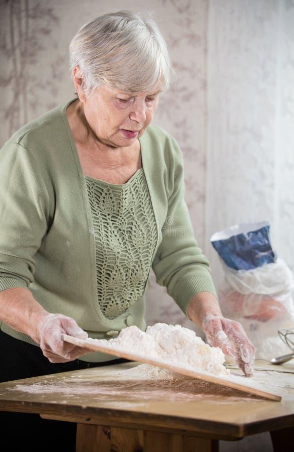 做小的饼的一个老妇人 面团揉 画象 图库摄影