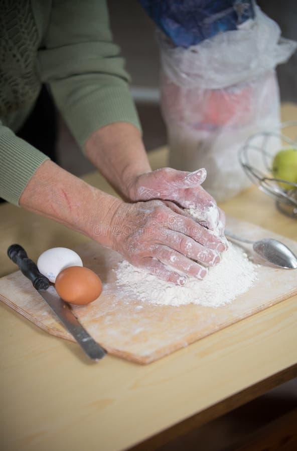 做小的饼的一个老妇人 面团揉 图库摄影
