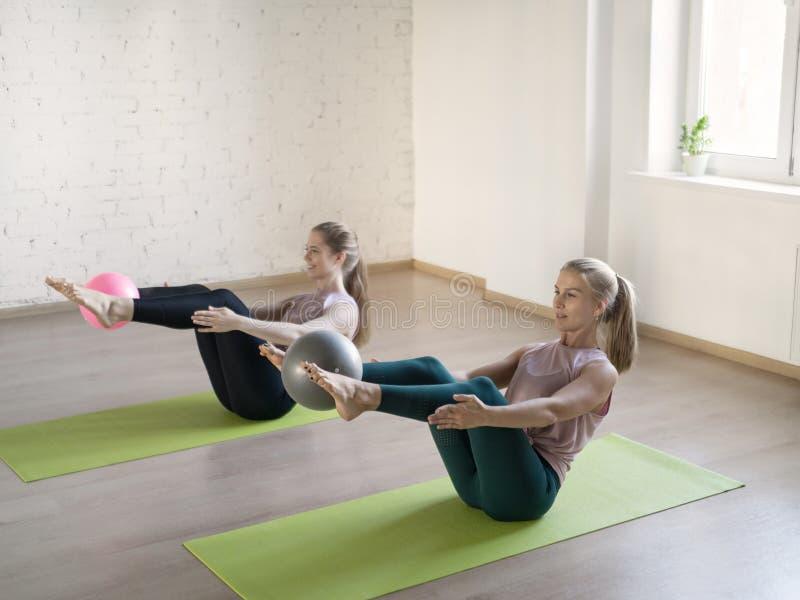 做小船姿势的两个白种人女孩在健身演播室,选择聚焦 免版税图库摄影
